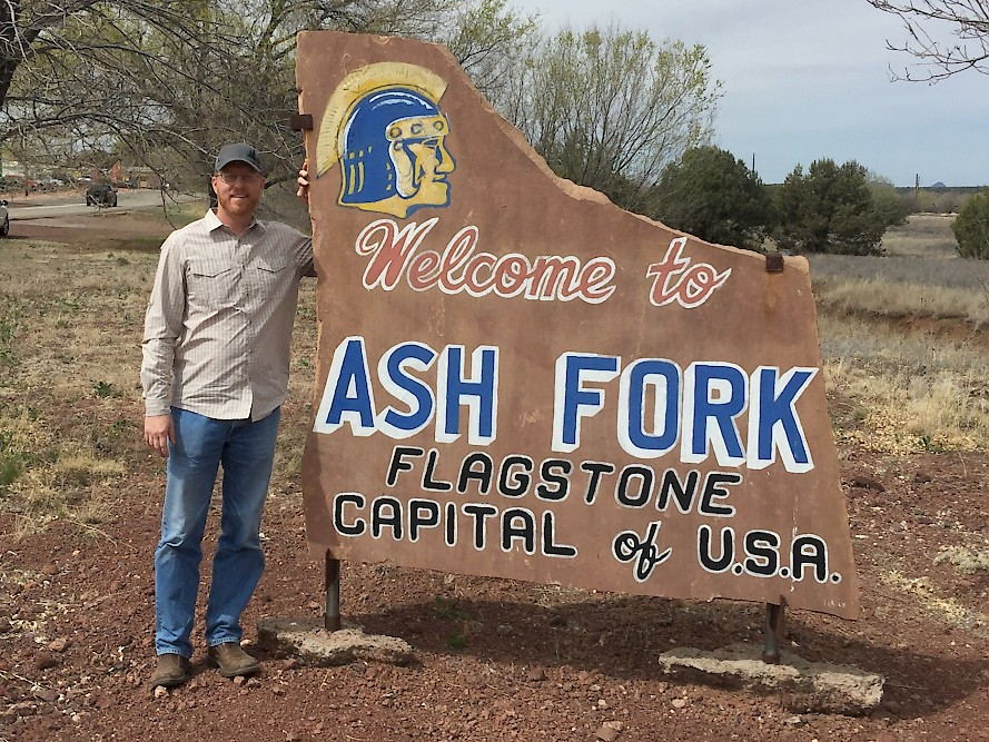 Joshua Fookes (President) poses by Ash Fork, AZ sign made out of flagstone